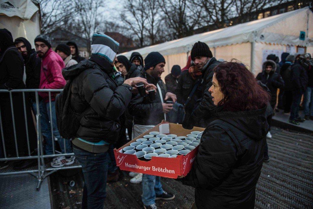 Vluchtelingen krijgen thee van een vrijwilliger. Bij het officiële uitdeelpunt voor thee is het water af Foto: Pieter Heijboer.