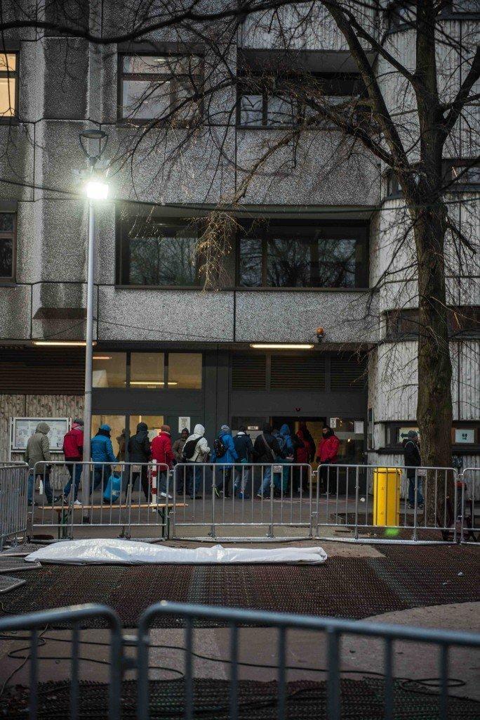 Deze groep vluchtelingen mag binnen in het aanmeldcentrum. Foto: Pieter Heijboer.